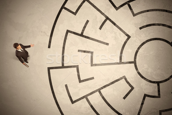 Lost business man looking for a way in circular labyrinth Stock photo © ra2studio