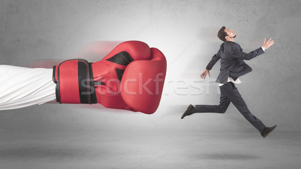 Stock photo: Businessman gets a hit from a giant hand