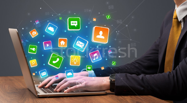 Stock photo: Hand using laptop with application icons flying around