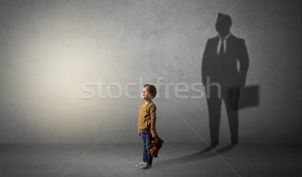 Little boy with businessman shadow Stock photo © ra2studio