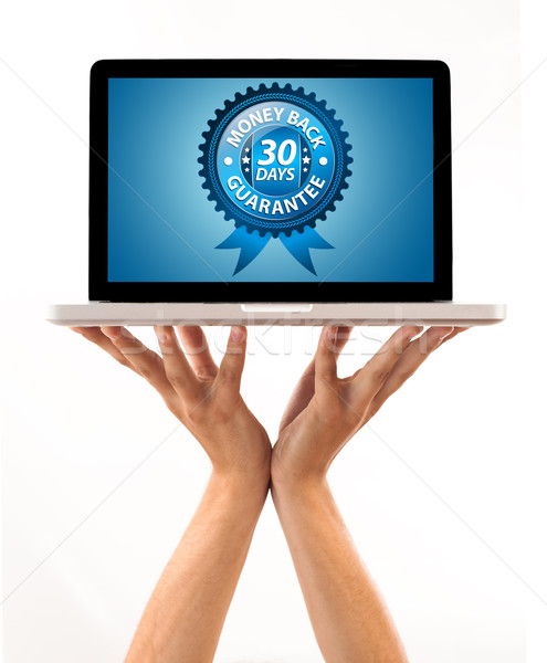 male hand holding a laptop with Money back Label Stock photo © ra2studio