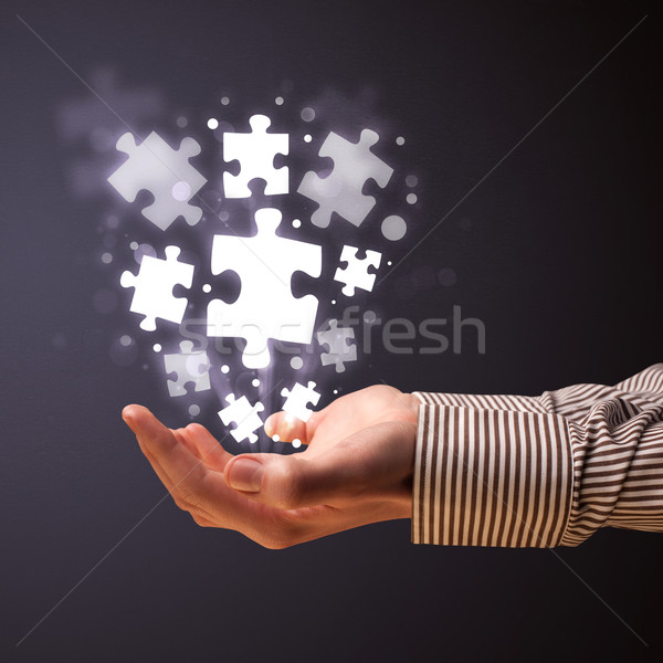 Puzzle pieces in the hand of a businessman Stock photo © ra2studio