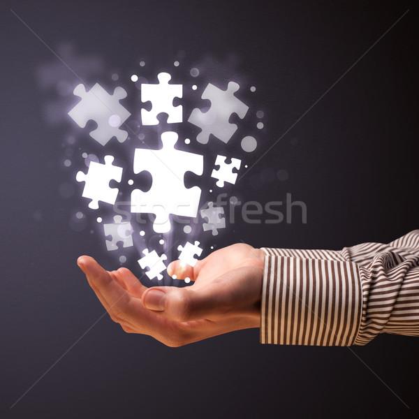 Kirakó darabok kéz üzletember tart ragyogó üzlet Stock fotó © ra2studio