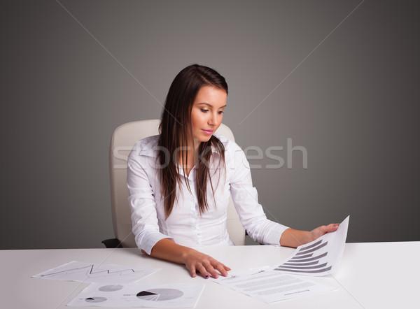 Businesswoman sitting at desk and doing paperwork Stock photo © ra2studio