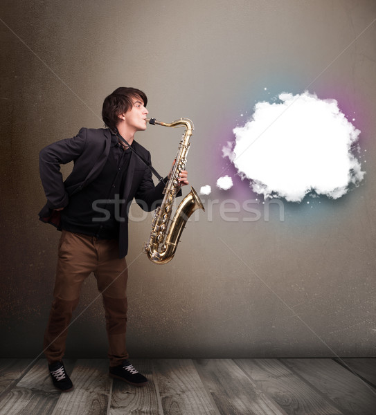 Young man playing on saxophone with copy space in white cloud Stock photo © ra2studio