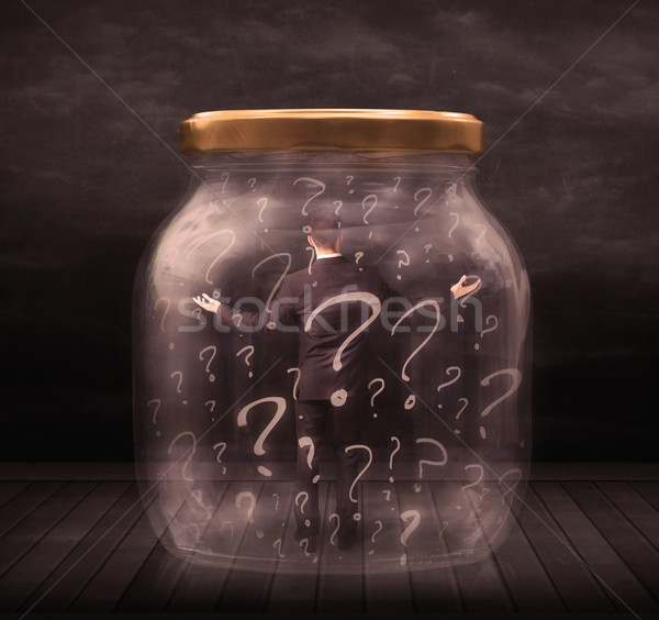 Stock photo: Businessman locked into a jar with question marks concept