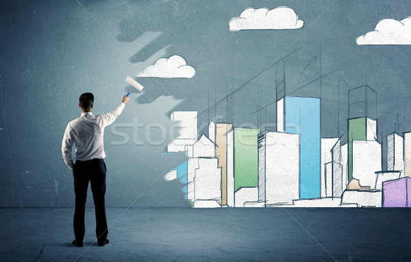 Salesman painting tall buildings on urban wall Stock photo © ra2studio