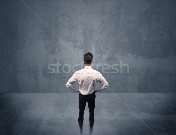 Businessman standing in front of urban wall Stock photo © ra2studio