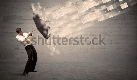 Business man protecting with umbrella against wind of papers Stock photo © ra2studio