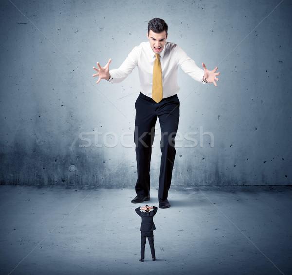 Angry huge business man lokking at small guy Stock photo © ra2studio