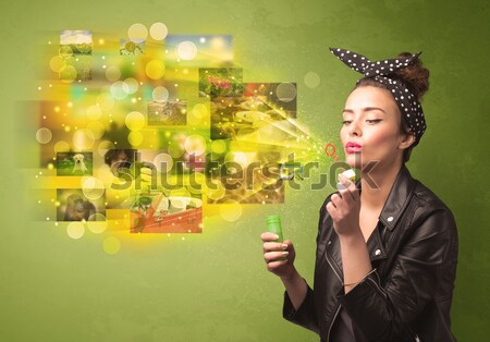 Stock photo: Cute girl blowing colourful glowing memory picture concept