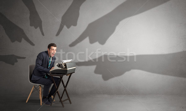 Shadow hands pointing at a small worker Stock photo © ra2studio