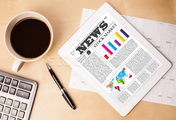 Stock photo: Tablet pc shows news on screen with a cup of coffee on a desk