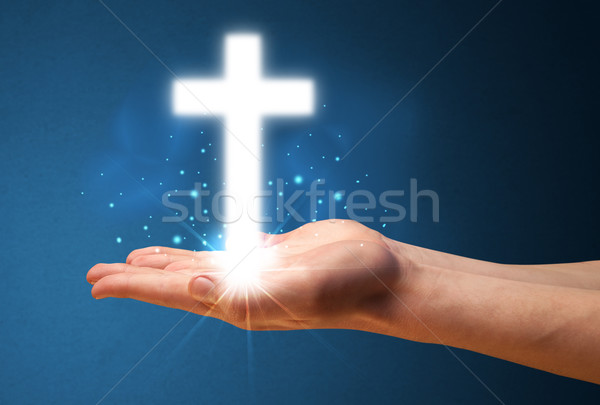 Glowing cross in the hand of a businessman Stock photo © ra2studio