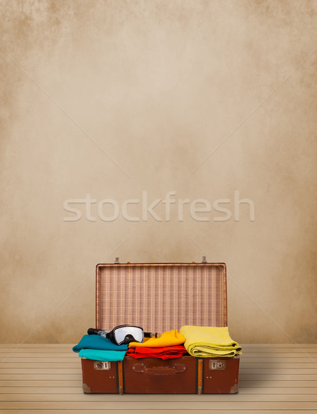 Retro tourist luggage with colorful clothes and copyspace Stock photo © ra2studio