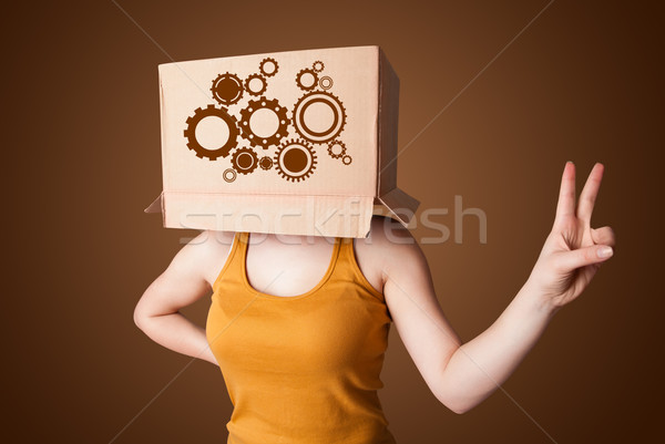 Young woman gesturing with a cardboard box on his head with spur Stock photo © ra2studio