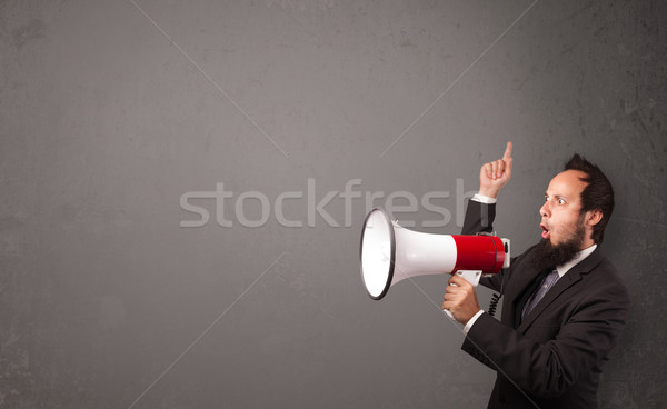 Guy shouting into megaphone on copy space background Stock photo © ra2studio