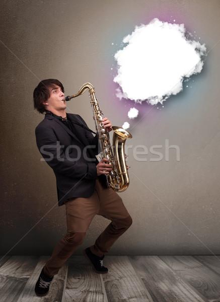 молодым человеком играет саксофон копия пространства белый облаке Сток-фото © ra2studio