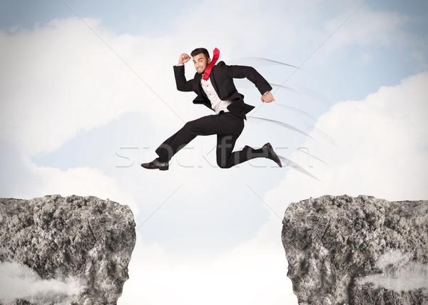 Funny człowiek biznesu skoki skał luka niebo Zdjęcia stock © ra2studio