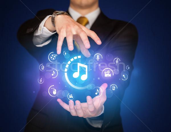Mann halten digitalen Multimedia Symbole Geschäftsmann Stock foto © ra2studio