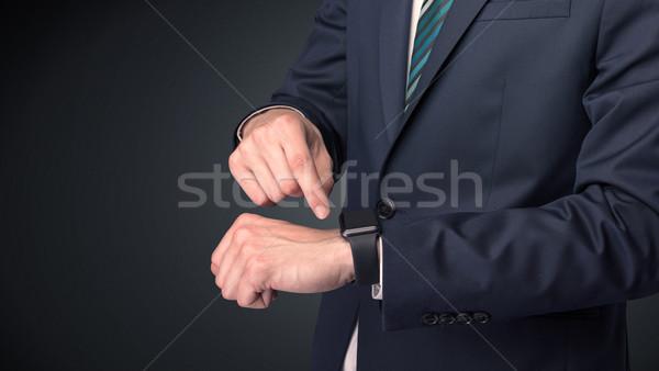 Man in suit wearing smartwatch. Stock photo © ra2studio
