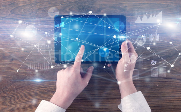 Hand holding tablet with linked graphs and charts concept Stock photo © ra2studio