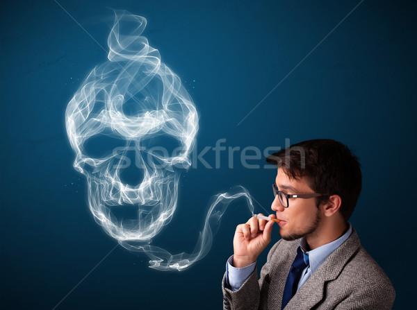 Jeune homme fumer dangereux cigarette toxique crâne Photo stock © ra2studio