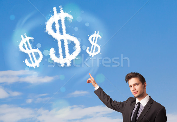 Businesman pointing at dollar sign clouds on blue sky  Stock photo © ra2studio