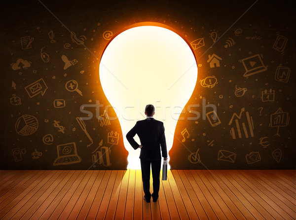Business man looking at bright light bulb in the wall  Stock photo © ra2studio