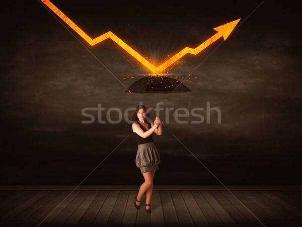 Businesswoman standing with umbrella keeping orange arrow  Stock photo © ra2studio