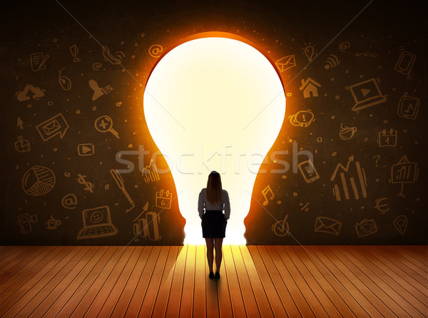 Business woman looking at bright light bulb in the wall  Stock photo © ra2studio