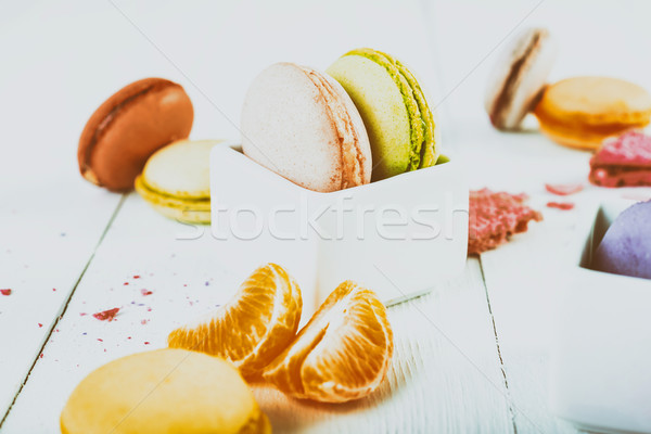 French Macaroons With Tangerine Slices On Wood Table Stock photo © radub85