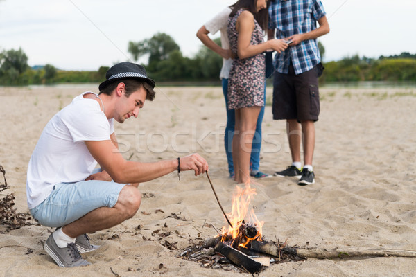 Amis suspendu autour feu de joie plage de sable Photo stock © rafalstachura