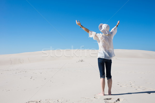 Woman lifting her hands up in the air standing on sand dune Stock photo © rafalstachura