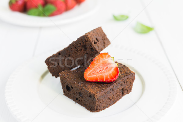 Chocolate brownie cake on white plate decorated with strawberrie Stock photo © rafalstachura