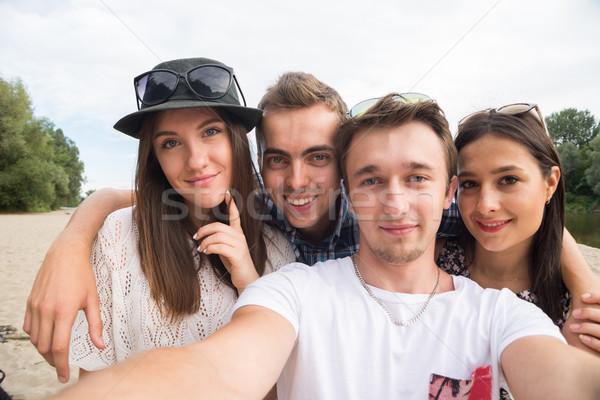 Fiatal mosolyog barátok elvesz homokos tengerpart csoport Stock fotó © rafalstachura