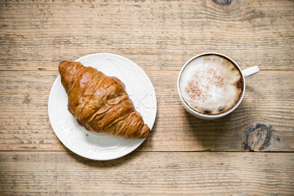 Cup of cafe latte and croissant on wooden table Stock photo © rafalstachura