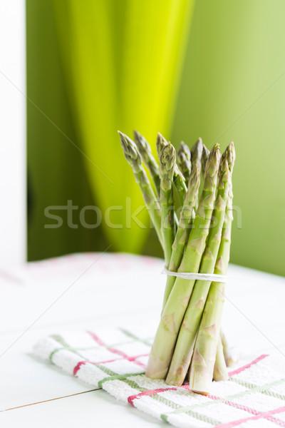 Bunch of fresh asparagus standing on kitchen cloth and white tab Stock photo © rafalstachura