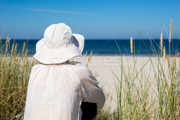 Woman sitting on sand dune and looking at sea Stock photo © rafalstachura
