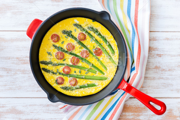Frittata with fresh asparagus and cherry tomatoes. Top view Stock photo © rafalstachura