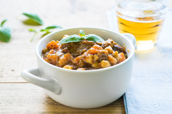 Beef stew with chickpeas and carrots in a white bowl on a wooden Stock photo © rafalstachura