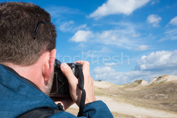 Rear view of a man photographying landscape with digital camera Stock photo © rafalstachura