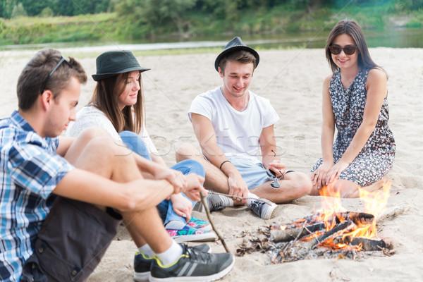 Fiatal felnőtt barátok akasztás körül máglya homokos tengerpart Stock fotó © rafalstachura