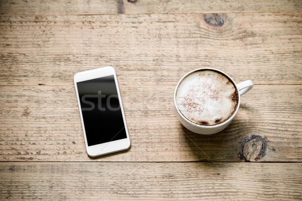 Beker cafe witte smartphone houten tafel koffie Stockfoto © rafalstachura