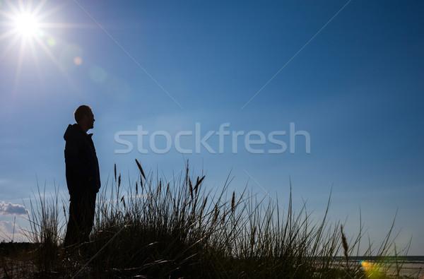 Hombre pie duna mirando mar silueta Foto stock © rafalstachura