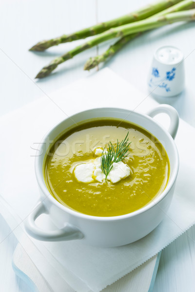 Bowl of asparagus soup topped with fresh cream and dill Stock photo © rafalstachura