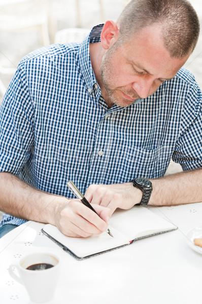 Homme écrit portable séance table tasse Photo stock © rafalstachura