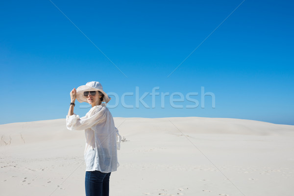 Woman wearing hat and sunglasses standing on sand dune Stock photo © rafalstachura
