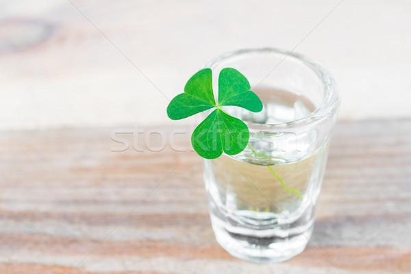Három levél shamrock üveg fa asztal közelkép Stock fotó © rafalstachura
