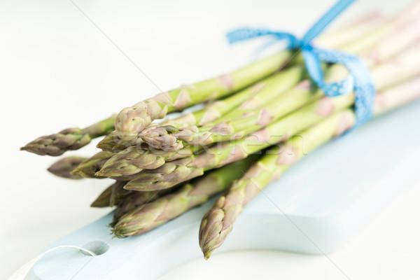 Bunch of fresh asparagus on a blue wooden cutting board Stock photo © rafalstachura